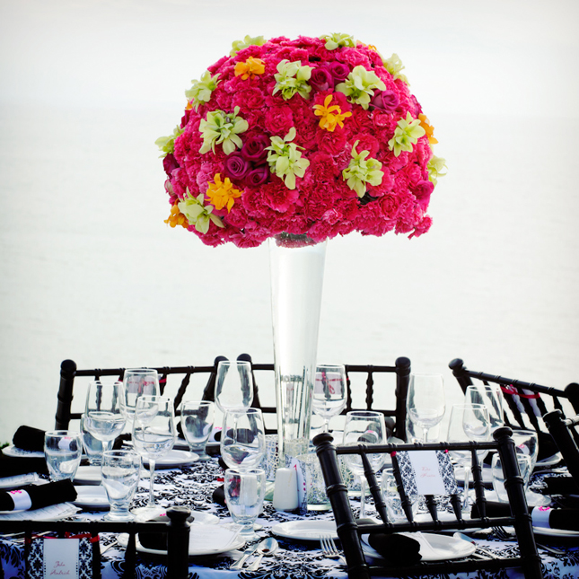 a black and white tablescape with patterns and a bright floral centerpiece for a colorful touch
