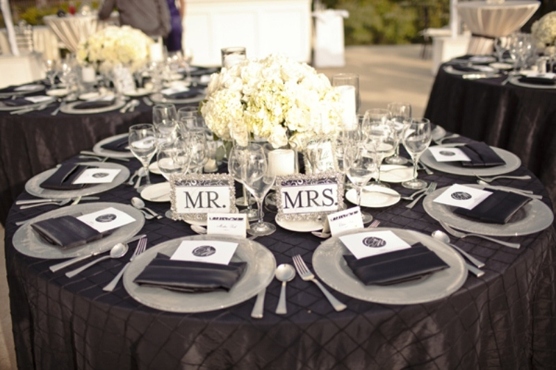 a black, white and silver wedding tablescape with a lush floral centerpiece