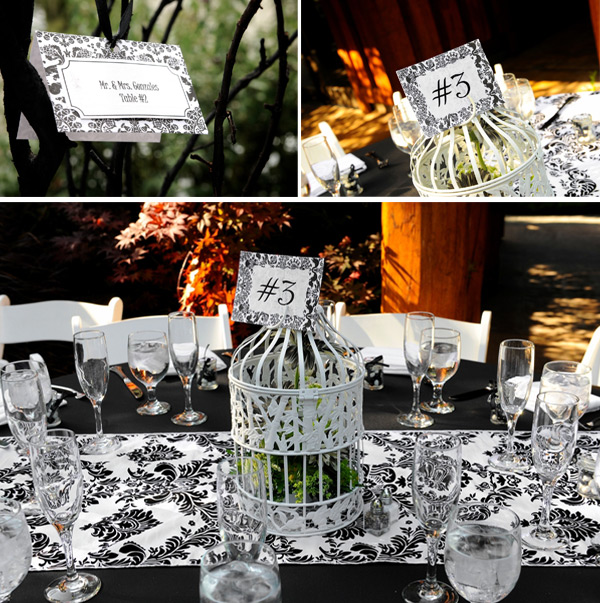 a chic black and white wedding tablescape with a printed table runner, a cage and stationery