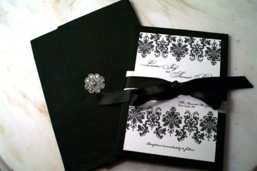 black and white wedding stationery with patterns, bows and a brooch looks very elegant