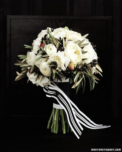 a black and white wedding bouquet with berries and striped ribbons
