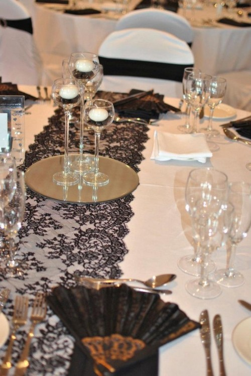 a white tablecloth, a black runner, black and white candles, black fans