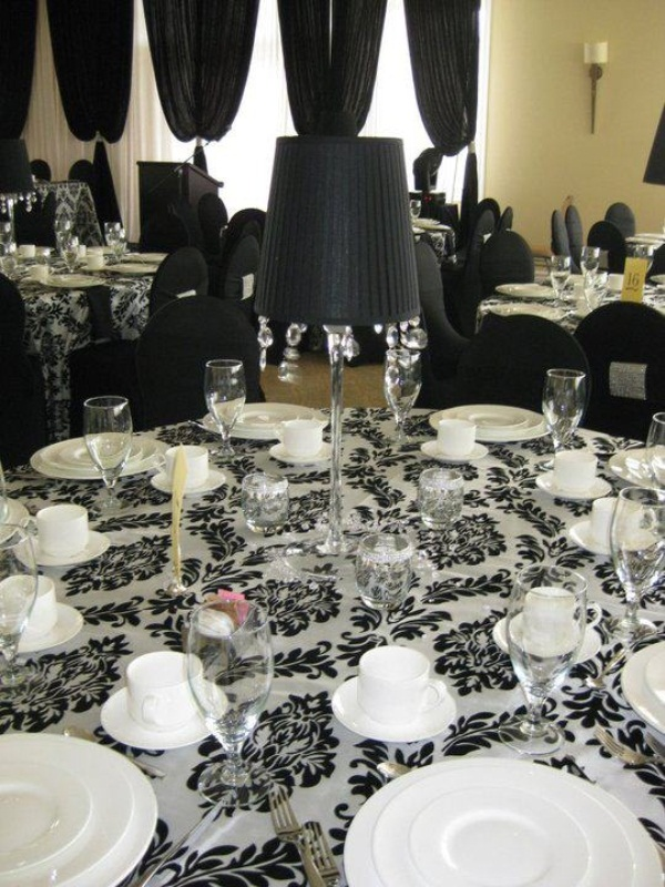 a black and white patterned tablecloth, a black lamp with crystals for decor