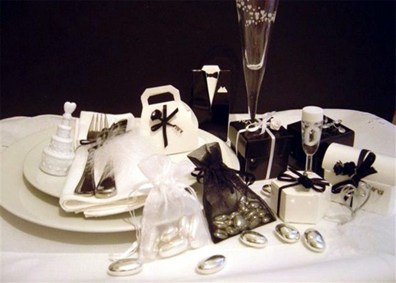 a black and white wedding favor table with glasses and bows is elegance