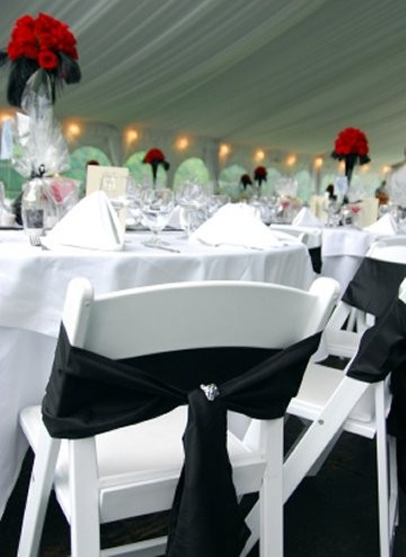 a white tablescape, white chairs and a black bow on the chair