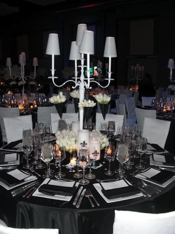 a black and white tablescape and a white table lamp with hanging black cones with blooms