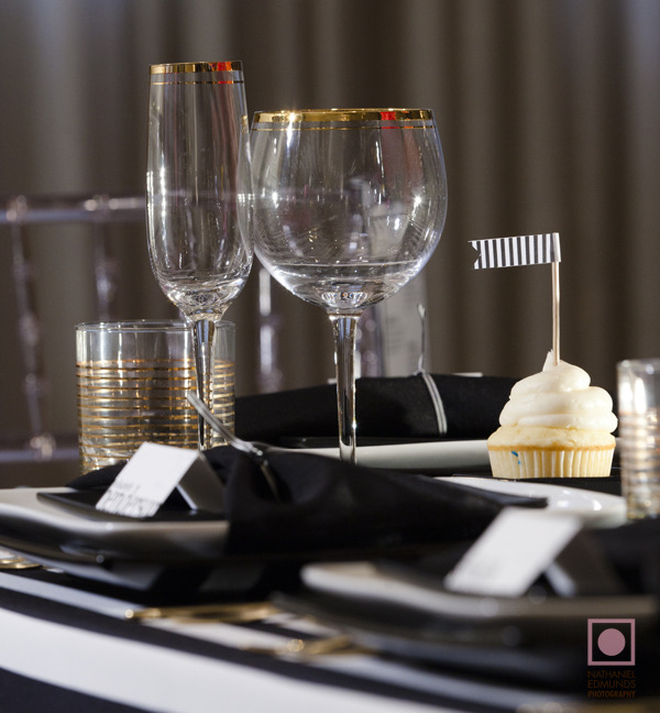 a simple place setting with white chargers, black napkins and gilded touches for more chic