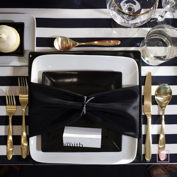 a stylish wedding place setting with a black and white tablecloth, gold cutlery and black and white plates
