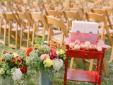 decorate your outdoor wedding ceremony space with bright fall blooms in buckets and a red stand with fresh apples for a fall feel