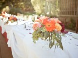 a bright fall floral wedding centerpiece with foliage is a cute idea for a fall wedding