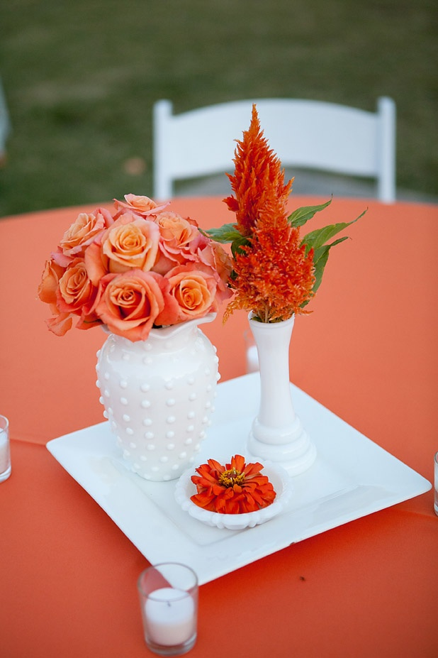 a bright fall floral centerpiece with touches of foliage and white porcelain