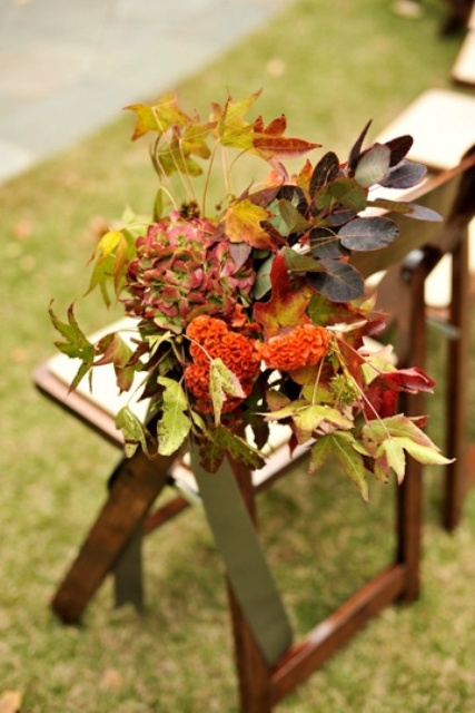 decorate the aisle chairs with bold fall foliage and blooms for your outdoor wedding ceremony