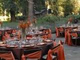 an outdoor reception space done in chocolate brown and rust, with rust-colored centerpieces and bright napkins