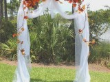 an outdoor fall wedding arch decorated with white fabric and lush and bright fall blooms and leaves