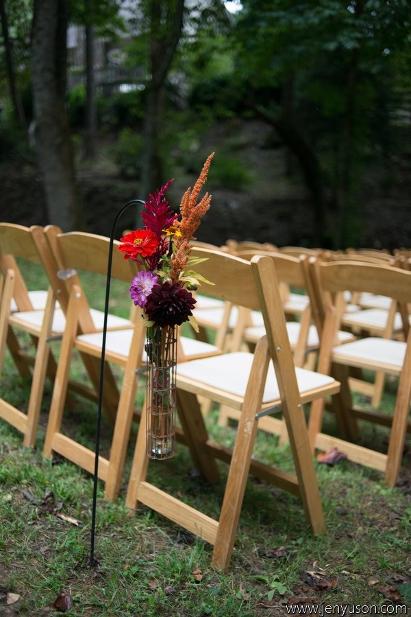 wedding aisle decor with bright and dark fall flowers in a vase