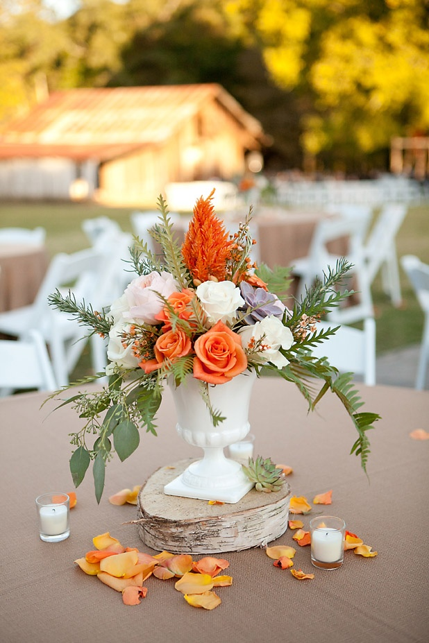 an elegant fall wedding centerpiece in blush, white, orange with foliage and succulents
