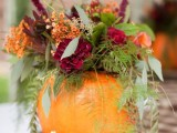 a rustic fall wedding centerpiece with a wood slice, a pumpkin with a bright fall floral arrangement and greenery