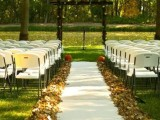 fall leaves lining up the outdoor wedding aisle and a couple of pumpkins in the end