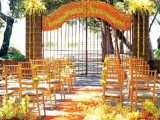 an outdoor fall wedding ceremony space decorated with bright and lush fall blooms and leaves and done with bright orange chairs