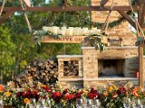 a chic rustic fall reception table with a box with candles, a bright floral table runner and rattan chairs