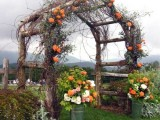 a wooden arch with vines, bright orange blooms and greenery plus bucket arrangements on each side