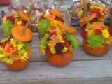 little pumpkins as vases for bright fall blooms is a creative wedding centerpiece idea