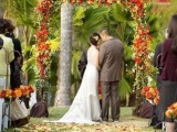 a bright fall floral wedding arch with fall leaves and some leaves on the ground