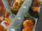 a fall wedding centerpiece with a log with candles and bright fall leaves, gourds and pumpkins