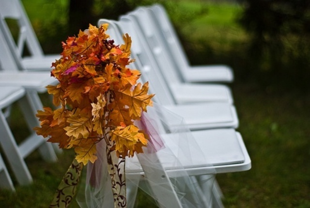 simple white chairs decorated with bright fall leaves and tulle for an outdoor wedding ceremony