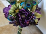 a bold purple and green wedding bouquet with peacock feathers incorporated