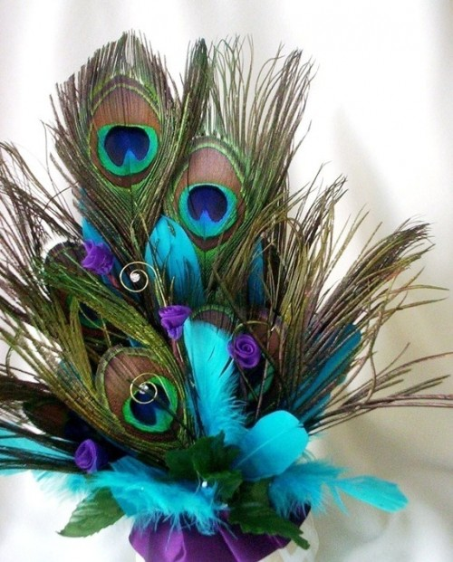a wedding centerpiece compsoed of peacock and turquoise feathers in a purple vase