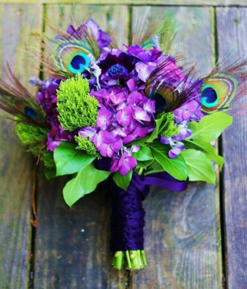 a purple and green wedding bouquet with peacock feathers and a purple wrap