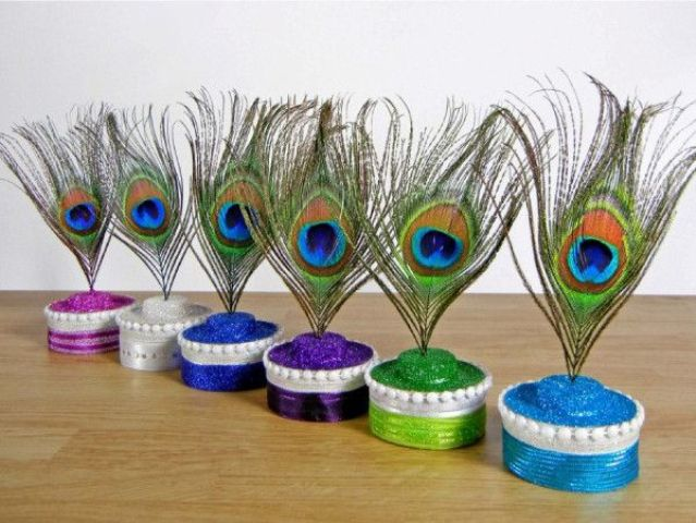 bright wedding decorations   colorful glitter stands with peacock feathers on top