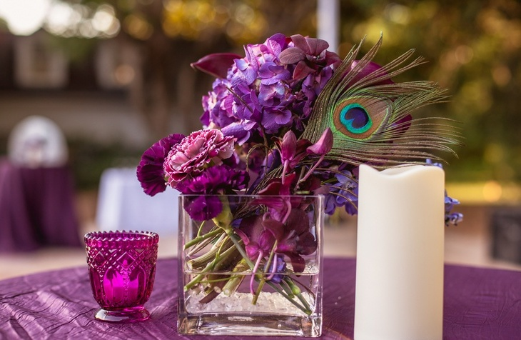 a purple floral wedding centerpiece accented with a peacock feather and candles around