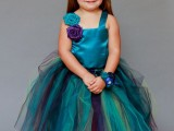 a bright teal flower girl dress with purple accents and a fun peacock feather hairpiece