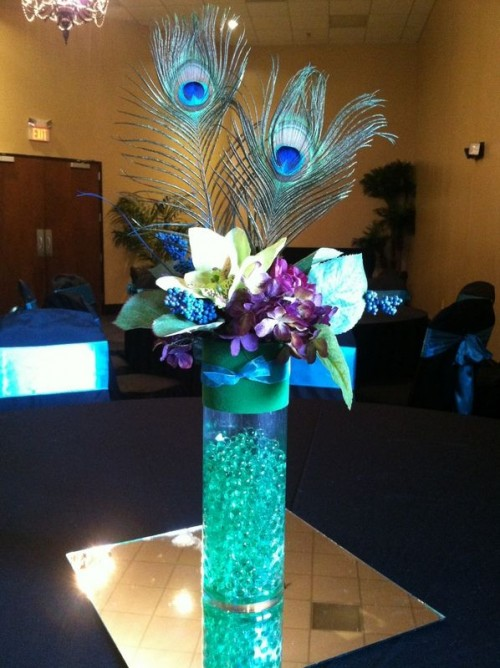 a turquoise wedding centerpiece with purple touches and peacock feathers