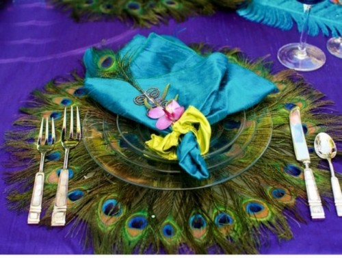 a bright wedding place setting done with a turquoise napkin and a peacock feather charger