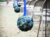 a peacock ball with a bright blue ribbon is a creative idea to accent a wedding aisle