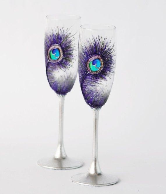 wedding flutes decorated with purple peacock feathers painted on them