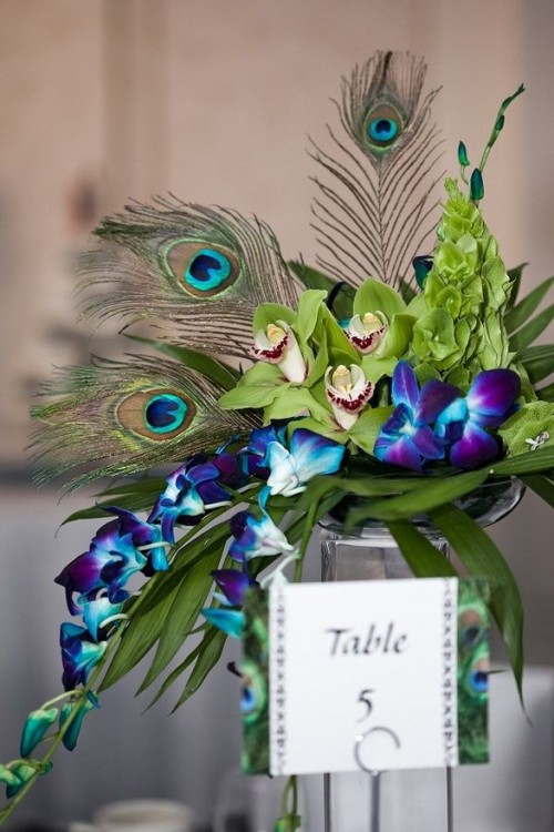 a bright wedding centerpiece with purple and green orchids and peacock feathers on a tall stand