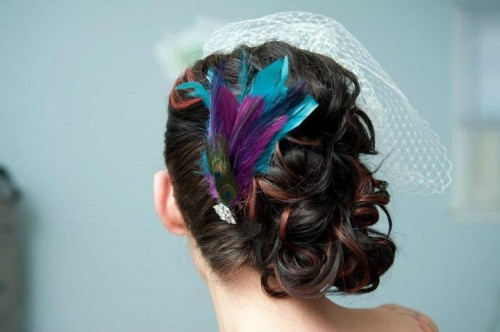 a bright wedding hairpiece of turquoise, purple and peacock feathers plus a cage veil on the other side