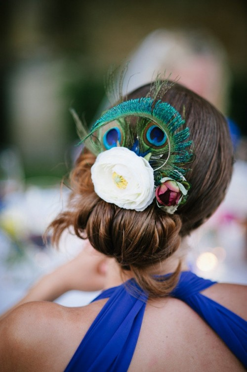 a low bun accented with fresh blooms and a peacock feather for a creative look
