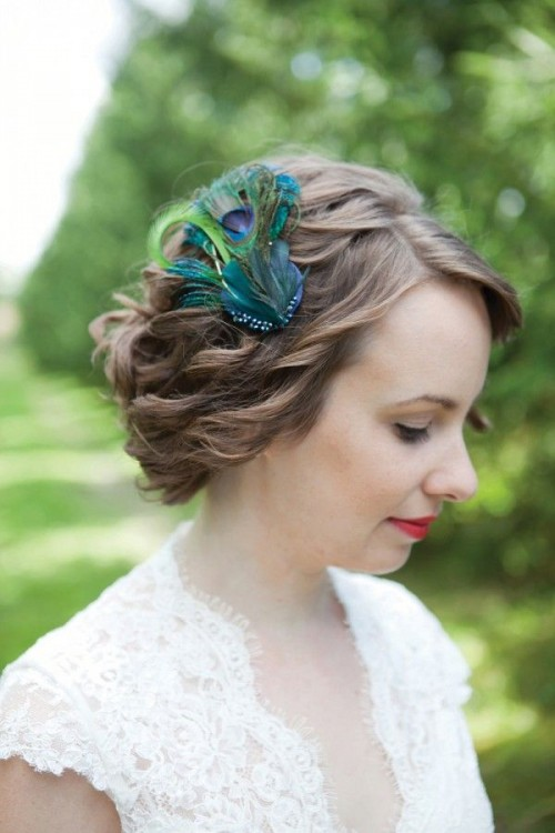 a wavy low updo highlighted with a single peacock feather is a very fun and whimsy idea