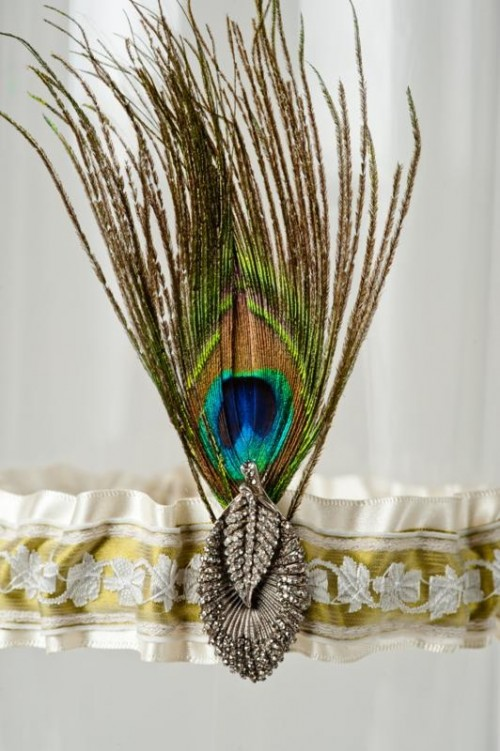 a wedding garter with a peacock feather and a vintage brooch is a unique accessory
