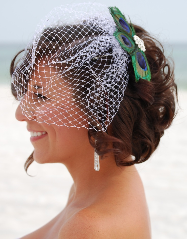 a birdcage veil with a vintage brooch and a peacock feather attached