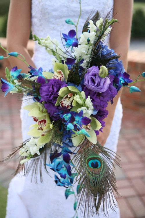 a bold cascading wedding bouquet done with green, purple and blue blooms and peacock feathers