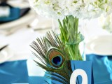 a wedding table number – a blue card with a peacock feather for an accent and better visibility