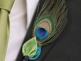 a peacock feather boutonniere plus a red and blue fabric leaf is a unique idea