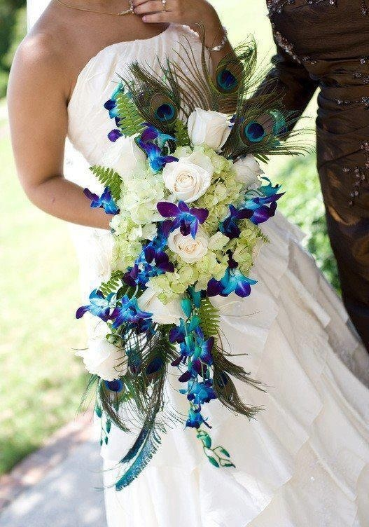 a bold cascading wedding bouquet of purple orchids, white hydrangeas and peacock feathers