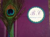 a purple wedidng album with a peacock feather for an accent to remind of your wedding theme